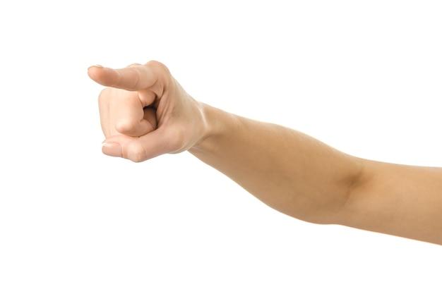 Wskazuje w lewo. kobieta ręka z francuskim manicure gestykuluje na białym tle na białej ścianie. część serii