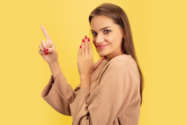 Wskazywanie. portret młodej kobiety kaukaski na żółtym tle