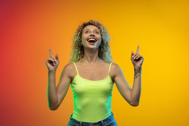 Wskazywanie. portret młodej kobiety rasy kaukaskiej na tle gradientu studio w neon. piękna modelka kręcone w stylu casual. pojęcie ludzkich emocji, wyraz twarzy, młodość, sprzedaż, reklama.