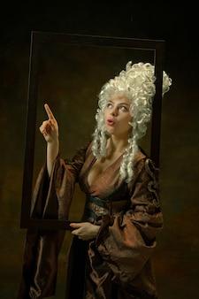 Wskazywanie. portret średniowiecznej młodej kobiety w odzież vintage z drewnianą ramą na ciemnym tle. modelka jako księżna, osoba królewska. pojęcie porównania epok, nowoczesności, mody, piękna.