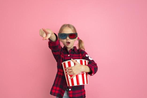 Wskazywanie w okularach 3d. kaukaski portret małej dziewczynki na różowej ścianie studio.