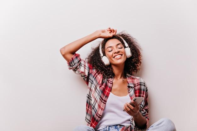 Wspaniała afrykańska dziewczyna trzyma smartfon i słucha muzyki. fascynująca modelka korzystająca z piosenki z zamkniętymi oczami.
