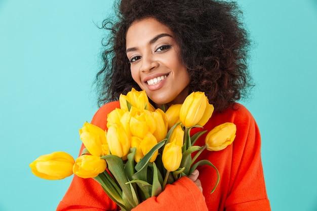 Wspaniała amerykańska kobieta z rozczochranymi włosami i trzymając bukiet pięknych żółtych kwiatów, odizolowanych na niebieskiej ścianie