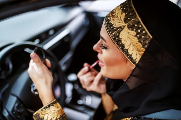 Wspaniała atrakcyjna młoda muzułmanka w tradycyjnym stroju siedzi w samochodzie podczas korka i nakłada szminkę.
