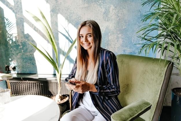 Wspaniała biała dziewczyna siedzi w fotelu z uśmiechem. seksowna kaukaska dama z telefonem pozuje w kawiarni z przyjemnością.