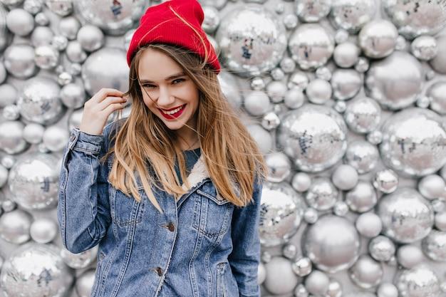 Wspaniała biała kobieta w stylowej dżinsowej kurtce z długimi włosami. uśmiechnięta podekscytowana dziewczyna w czerwonym kapeluszu stojącym przed kulkami disco.