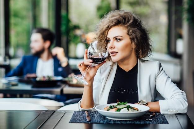 Wspaniała blond kobieta biznesu freelancer z kieliszkiem czerwonego wina je kolację w luksusowej restauracji