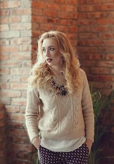 Wspaniała blond kobieta w beżowym swetrze