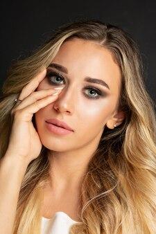 Wspaniała blondynka długowłosa kobieta z jasnym makijażem pozowanie w studio czarnym tle