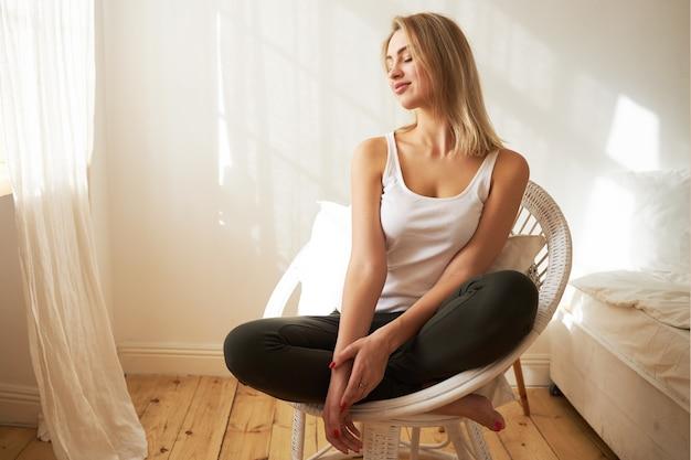 Wspaniała blondynka młoda kobieta w swobodnym ubraniu siedzi w fotelu ze złożonymi nogami, ma zrelaksowany, beztroski wyraz twarzy, patrzy przez okno, cieszy się ciepłym światłem słonecznym, trzymając zamknięte oczy