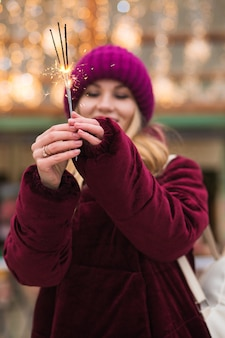 Wspaniała blondynka trzyma świecące światła bengalskie na jarmarku bożonarodzeniowym w kijowie. efekt rozmycia