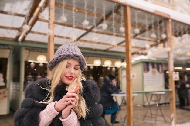 Wspaniała blondynka trzymająca aromatyczne świąteczne pierniczki na tle lekkiej dekoracji na jarmarku bożonarodzeniowym w kijowie