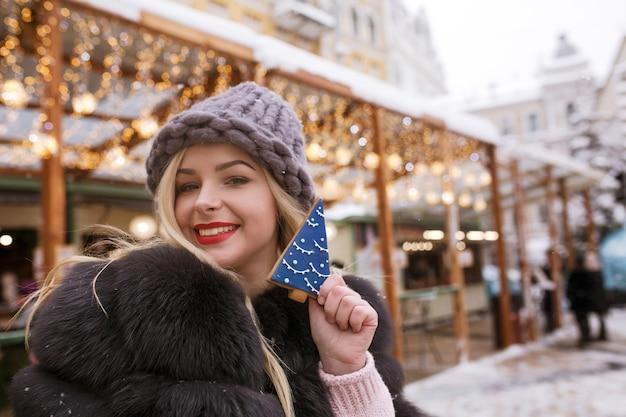 Wspaniała blondynka trzymająca pyszne pierniki na tle lekkiej dekoracji na jarmarku bożonarodzeniowym w kijowie