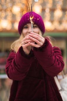 Wspaniała blondynka trzymająca świecące światła bengalskie na jarmarku bożonarodzeniowym w kijowie. efekt rozmycia