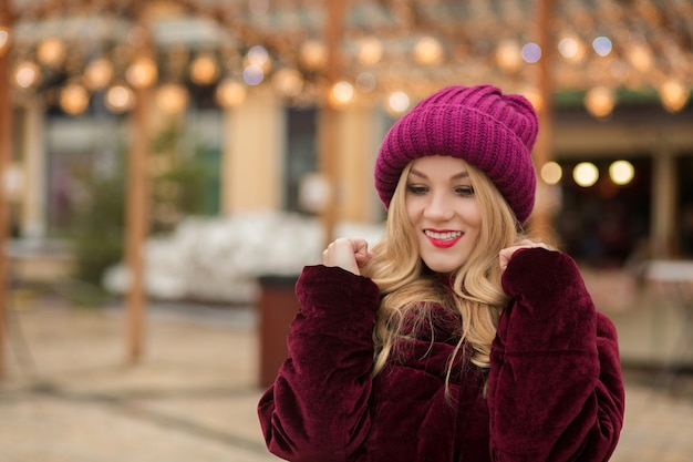 Wspaniała blondynka w czerwonej czapce z dzianiny i płaszczu zimowym, pozowanie na tle girlandy na ulicy w kijowie