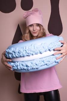 Wspaniała blondynka w różowej koszulce i czapce z dużym ciastem makaronikowym