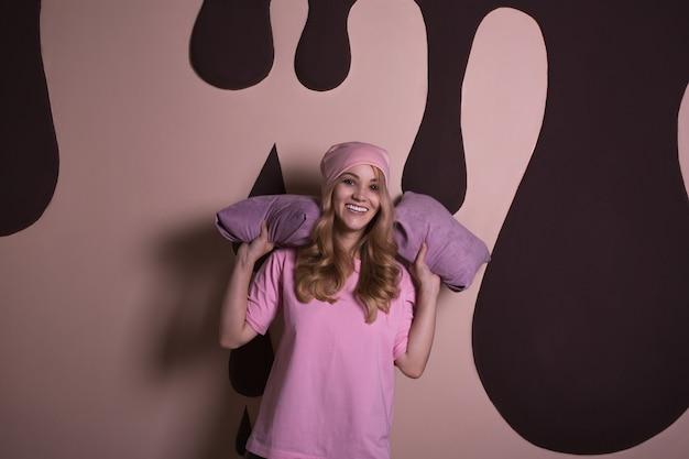 Wspaniała blondynka z kręconymi włosami bawiąca się poduszkami na różowym tle studyjnym