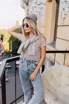Wspaniała blondynka z modną fryzurą stojąc na tarasie i patrząc na miasto rano