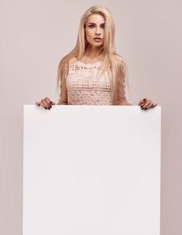 Wspaniała blondynki kobieta trzyma pustego billboard