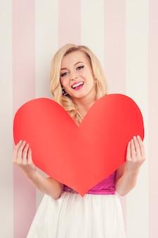 Wspaniała blondynki kobieta z dużym czerwonym sercem