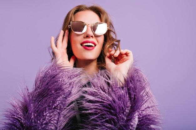 Wspaniała brązowowłosa dziewczyna w błyszczących okularach patrząc w górę z czarującym uśmiechem
