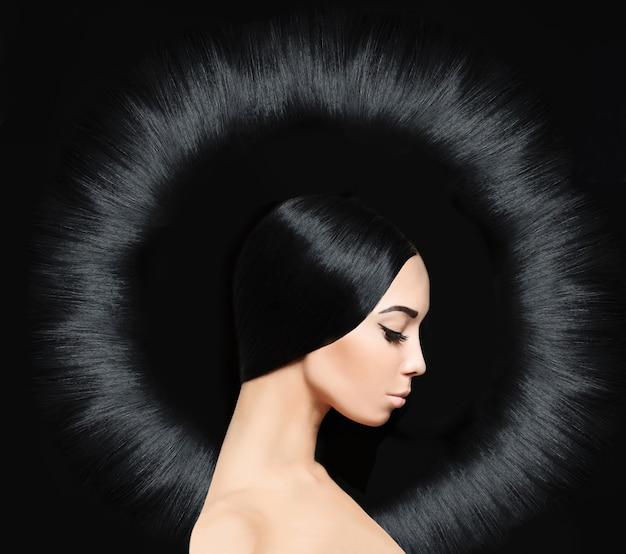 Wspaniała brunetka dama z długą błyszczącą fryzurą. salon fryzjerski w tle
