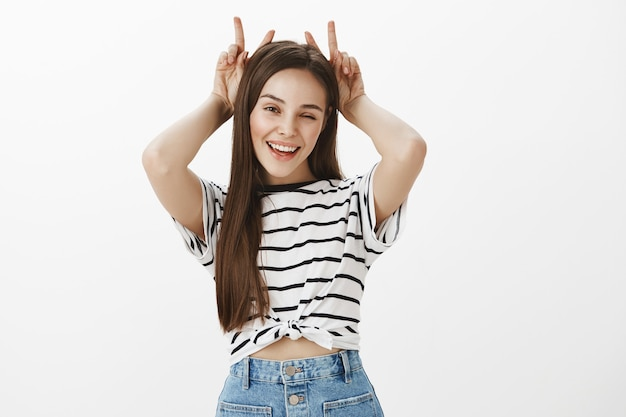 Wspaniała brunetka dziewczyna pokazuje gest rogów nad głową, działając figlarnie i zalotnie