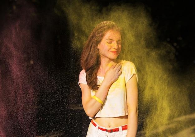 Wspaniała brunetka kobieta pozuje w chmurze żółtej suchej farby holi w parku