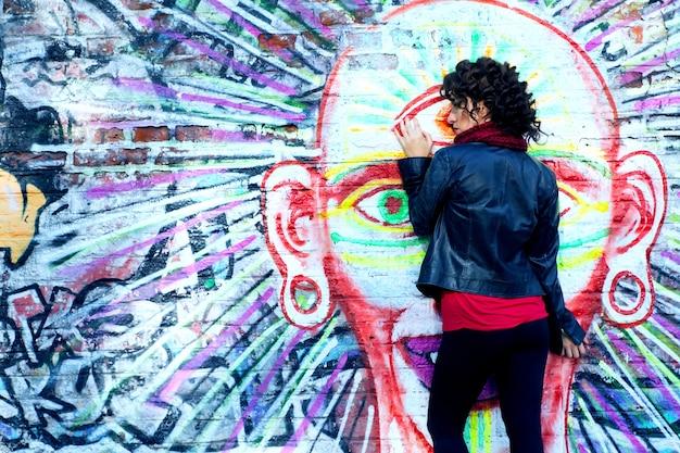 Wspaniała brunetka kobieta pozuje z duchową głową graffiti na ulicy.
