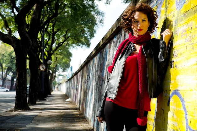 Wspaniała brunetka kobieta pozuje z graffiti na ulicy.