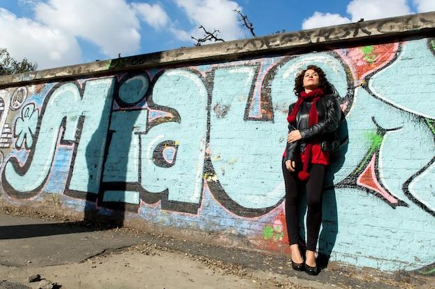 Wspaniała brunetka kobieta pozuje z niebieskim graffiti na ulicy.