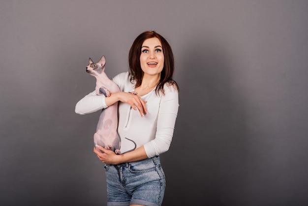Wspaniała brunetka kobieta uśmiechnięta, trzymając kotka sphynx