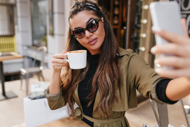 Wspaniała brunetka kobieta w okularach przeciwsłonecznych pije kawę i robi sobie zdjęcie w weekend