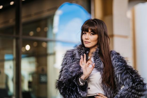 Wspaniała brunetka kobieta z długimi prostymi włosami ubrana w szary futro, białą koszulę i czarną spódnicę dobrze gest na tle okna sklepu. zadowolony z zakupów.