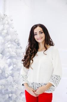 Wspaniała brunetka kobieta z doskonałym makijażem i gładką skórą ubrana w szary sweter pozowanie