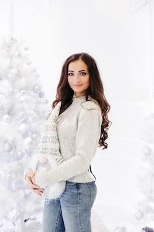 Wspaniała brunetka kobieta z doskonałym makijażem i gładką skórą w szarym swetrze pozuje w urządzonym studio