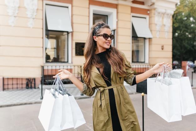 Wspaniała brunetka kobieta z romantyczną fryzurą pozuje z zaskoczonym wyrazem twarzy, trzymając papierowe torby