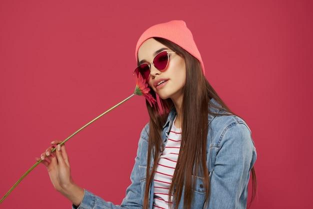 Wspaniała brunetka w różowym kapeluszu czerwony kwiat luksusowy na białym tle