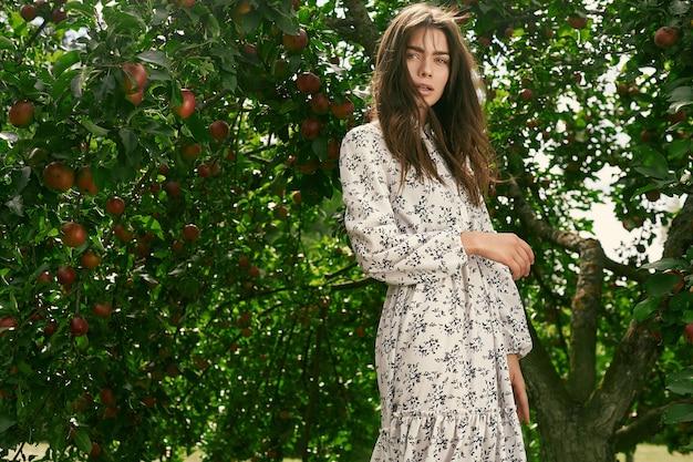 Wspaniała brunetki kobieta w moda klasyka sukni w jabłko ogródzie