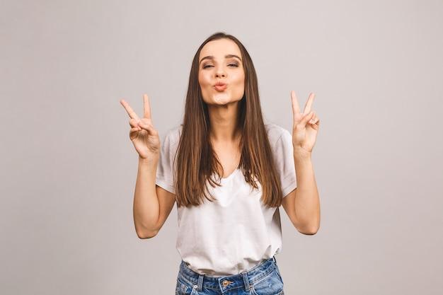 Wspaniała brunetki kobieta z uśmiechem i pokazuje palcami znak pokoju