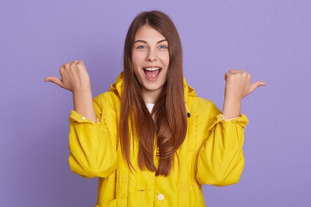 Wspaniała, całkiem urocza, urocza kobieta z długimi włosami w przypadkowej żółtej koszuli, wskazująca na bok dwiema rękami, stojąca odizolowana na liliowej ścianie.