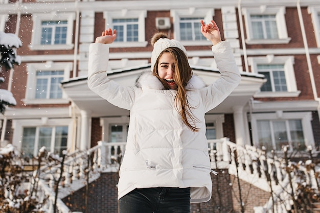 Wspaniała ciemnowłosa kobieta skacząca przed domem. zewnątrz zdjęcie śliczna młoda kobieta