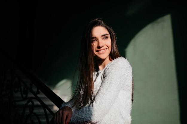 Wspaniała długowłosa dziewczyna z natchnionym uśmiechem odwracająca wzrok