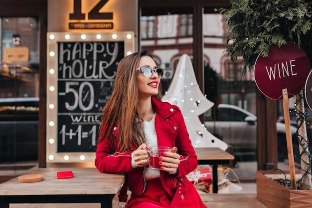 Wspaniała długowłosa modelka siedzi w kawiarni w wiosenny dzień