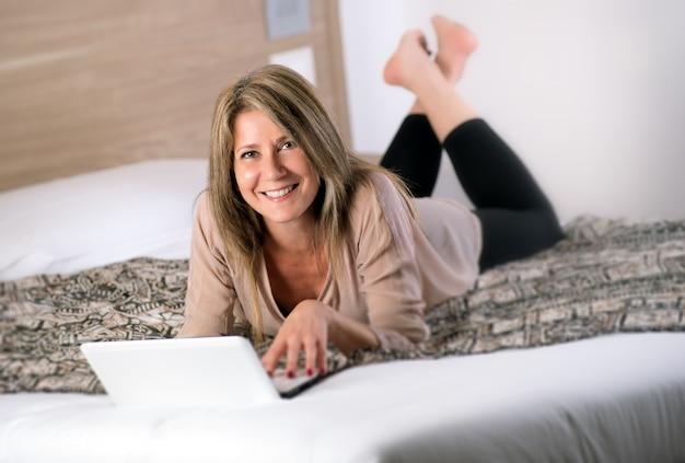 Wspaniała dojrzała kobieta kłaść na łóżku z laptopem