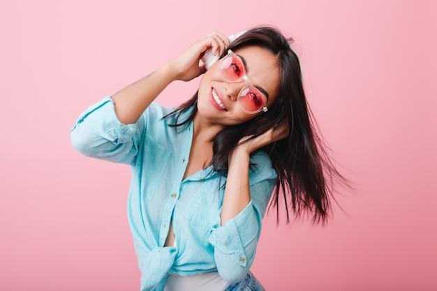 Wspaniała dziewczyna azjatyckich z wyrazem twarzy szczęśliwy macha włosami podczas słuchania muzyki. śliczne hiszpańskie modelki chłodzenie ulubioną piosenką.