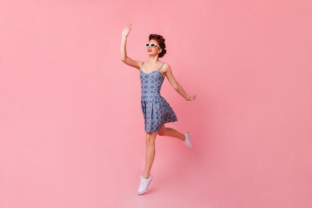 Wspaniała dziewczyna macha ręką w okularach przeciwsłonecznych. studio strzałów szczęśliwej kobiety pinup skoki na różowej przestrzeni.