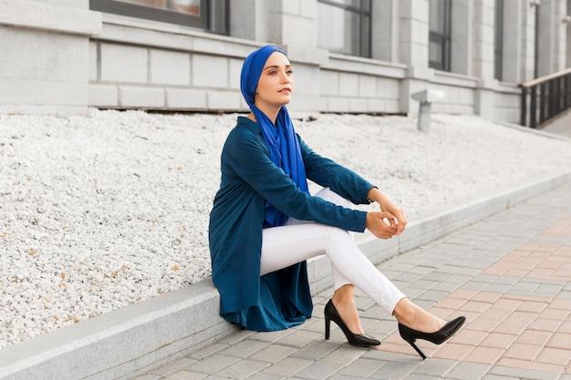 Wspaniała dziewczyna siedzi na zewnątrz z hidżabem