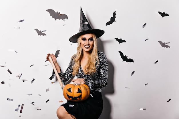 Wspaniała dziewczyna w błyszczącej bluzce trzyma dyni halloween. kryty zdjęcie uśmiechniętej, zadowolonej wiedźmy w czarnym kapeluszu.