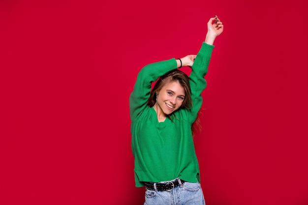 Wspaniała dziewczyna z długimi włosami, taniec z uśmiechem na czerwonym tle. wewnątrz portret inspirowanej kaukaskiej kobiety w zimowym stroju wyrażająca szczęśliwe emocje.